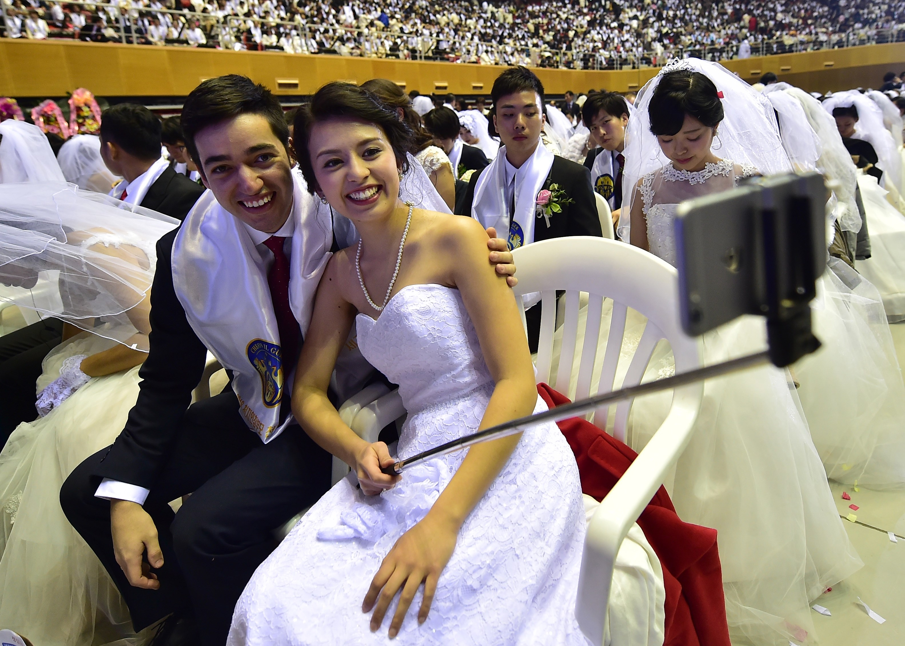"""A couple take a selfie during a mass wedding held by the Unification Church at Cheongshim Peace World Center in Gapyeong, east of Seoul, on February 20, 2016. Hundreds of couples were married at the South Korean headquarters of the Unification Church. The Unification Church, set up by Sun Myung Moon in Seoul in 1954, is one of the world's most controversial religious organisations, and its devotees are often dubbed """"Moonies"""" after the founder. AFP PHOTO / JUNG YEON-JE SKOREA--RELIGION-UNIFICATION-MARRIAGE"""