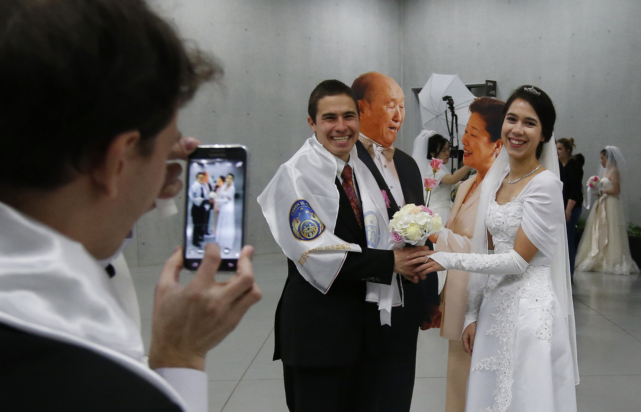 A couple have their souvenir photo taken near the cutout pictures of late Rev. Sun Myung Moon, the founder of the Unification Church and wife Hak Ja Han Moon before their mass wedding ceremony at the Cheong Shim Peace World Center in Gapyeong, South Korea, Saturday, Feb. 20, 2016. Three thousand of couples from more than 60 countries attended and other 12,000 couples participated in the Unification Church's mass wedding via live-streamed broadcast, according to the church, arranged by Hak Ja Han Moon. (AP Photo/Lee Jin-man) South Korea Mass Wedding