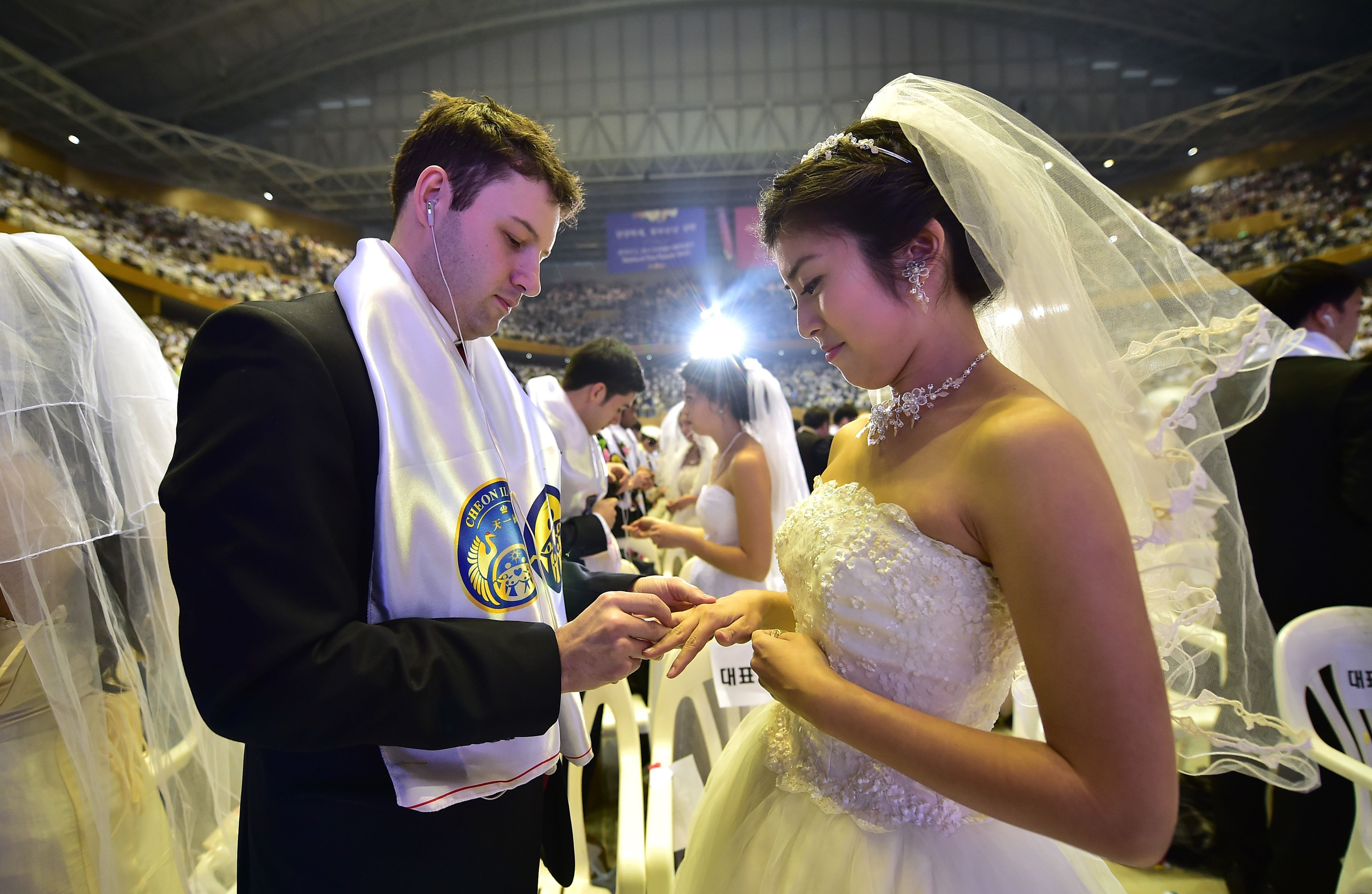 "A groom puts a ring on the finger of his bride during a mass wedding held by the Unification Church at Cheongshim Peace World Center in Gapyeong, east of Seoul, on February 20, 2016. Hundreds of couples were married at the South Korean headquarters of the Unification Church. The Unification Church, set up by Sun Myung Moon in Seoul in 1954, is one of the world's most controversial religious organisations, and its devotees are often dubbed ""Moonies"" after the founder. AFP PHOTO / JUNG YEON-JE SKOREA--RELIGION-UNIFICATION-MARRIAGE"