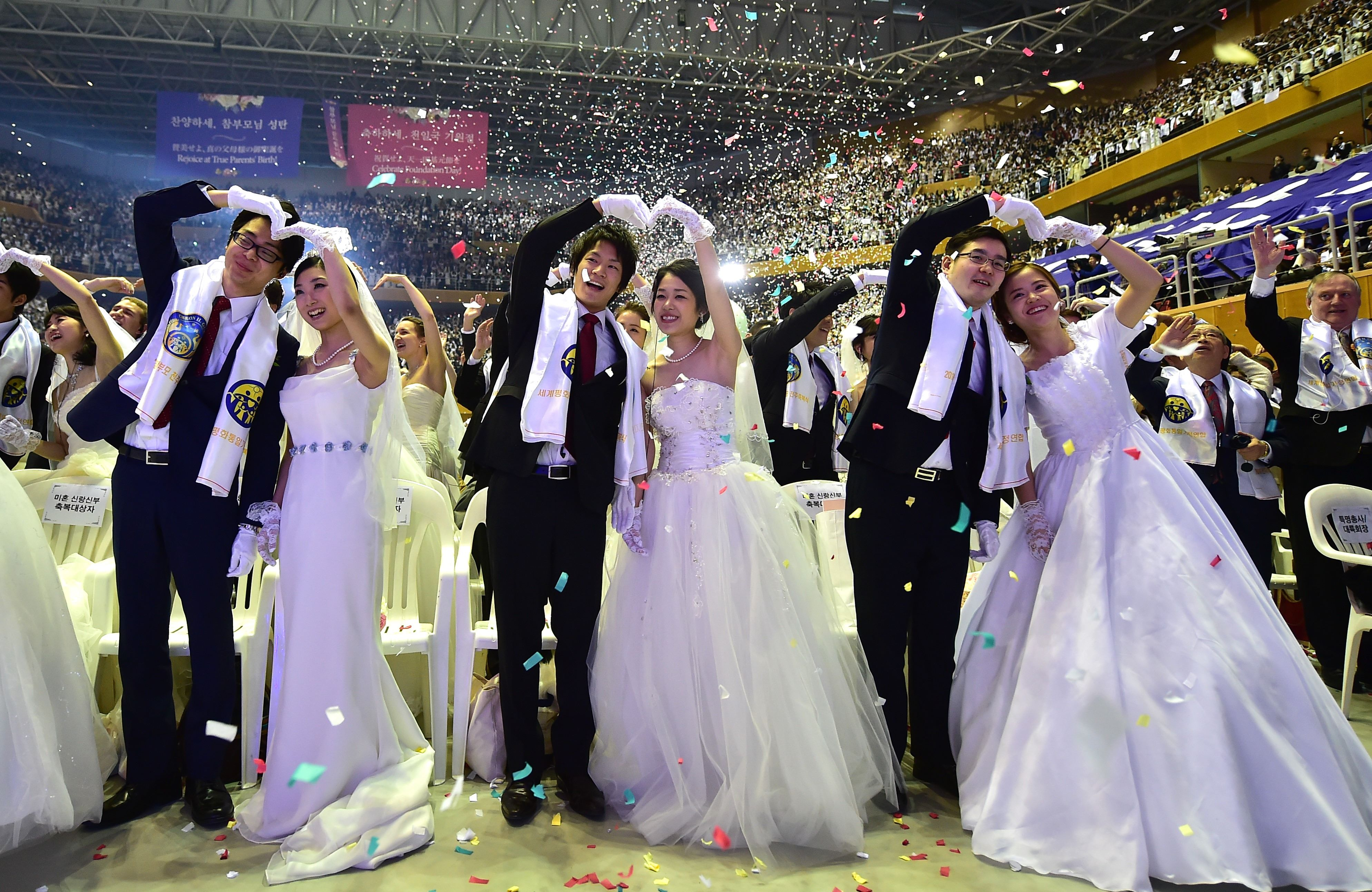 """Couples celebrate during a mass wedding held by the Unification Church at Cheongshim Peace World Center in Gapyeong, east of Seoul, on February 20, 2016. Hundreds of couples were married at the South Korean headquarters of the Unification Church. The Unification Church, set up by Sun Myung Moon in Seoul in 1954, is one of the world's most controversial religious organisations, and its devotees are often dubbed """"Moonies"""" after the founder. AFP PHOTO / JUNG YEON-JE SKOREA--RELIGION-UNIFICATION-MARRIAGE"""