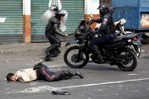 A police officer lies on the street after being run over by a bus during a protest against the increase in the price of public transport in San Cristobal