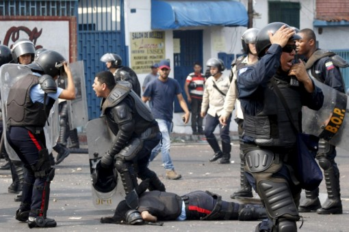 A police officer talks via radio next to a partner run over by a bus during a protest against the increase in the price of public transport in San Cristobal