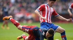 Atletico Madrid's Argentinian forward Luciano Vietto (L) falls next to Sporting Gijon's defender Jorge Mere during the Spanish league football match Real Sporting de Gijon vs Club Atletico de Madrid at El Molinon stadium in Gijon on March 19, 2016. / AFP PHOTO / MIGUEL RIOPA