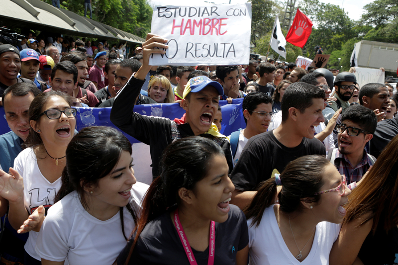 "Student protesters shout during a rally to demand increased university funding in Caracas, Venezuela, May 26, 2016. The placard reads ""Studying with hunger does not pay off"". REUTERS/Marco Bello"