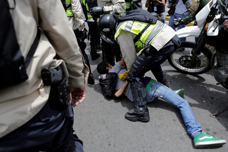 Riot police officers detain a demonstrator during clashes with opposition supporters in a rally to demand a referendum to remove President Nicolas Maduro in Caracas, Venezuela, May 18, 2016. REUTERS/Marco Bello