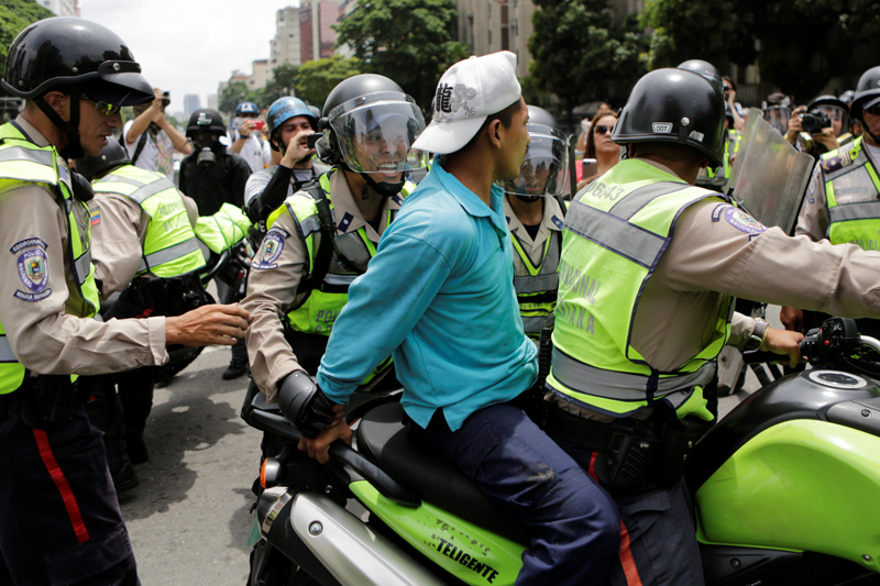 Riot police officers detain a demonstrator on a motorcycle during clashes with opposition supporters in a rally to demand a referendum to remove President Nicolas Maduro in Caracas, Venezuela, May 18, 2016. REUTERS/Marco Bello