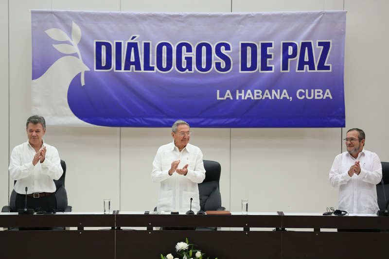 Cuba's President Raul Castro (C), Colombia's President Juan Manuel Santos (L) and FARC rebel leader Rodrigo Londono, better known by the nom de guerre Timochenko, react during the beginning of the ceremony to sign a historic ceasefire deal in Havana, Cuba, June 23, 2016. REUTERS/Alexandre Meneghini