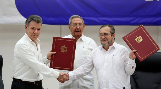 Cuba's President Raul Castro (C), Colombia's President Juan Manuel Santos (L) and FARC rebel leader Rodrigo Londono, better known by his nom de guerre Timochenko, react after signing a historic ceasefire deal between the Colombian government and FARC rebels in Havana, Cuba, June 23, 2016. REUTERS/Alexandre Meneghini      TPX IMAGES OF THE DAY