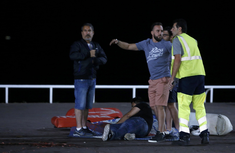 ATTENTION EDITORS - VISUAL COVERAGE OF SCENES OF INJURY OR DEATH - An injured individual is seen on the ground after at least 30 people were killed in Nice, France, when a truck ran into a crowd celebrating the Bastille Day national holiday July 14, 2016. REUTERS/Eric Gaillard