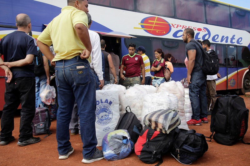 People stand next to bags filled with staple items and their luggage while they wait for transportation, after arriving from Brazil, at the bus terminal in Santa Elena de Uairen, Venezuela August 2, 2016. Picture taken August 2, 2016. REUTERS/William Urdaneta          FOR EDITORIAL USE ONLY. NO RESALES. NO ARCHIVES.
