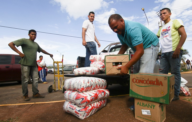 Men load boxes of food onto the back of a pick-up truck, after arriving from Brazil, in front of the bus terminal in Santa Elena de Uairen, Venezuela August 2, 2016. Picture taken August 2, 2016. REUTERS/William Urdaneta FOR EDITORIAL USE ONLY. NO RESALES. NO ARCHIVES.