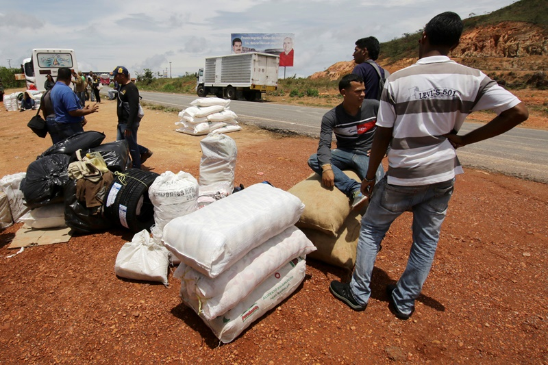 People stand next to bags filled with staple items while they wait for transportation in Santa Elena de Uairen, Venezuela August 3, 2016. Picture taken August 3, 2016. REUTERS/William Urdaneta FOR EDITORIAL USE ONLY. NO RESALES. NO ARCHIVES.     TPX IMAGES OF THE DAY