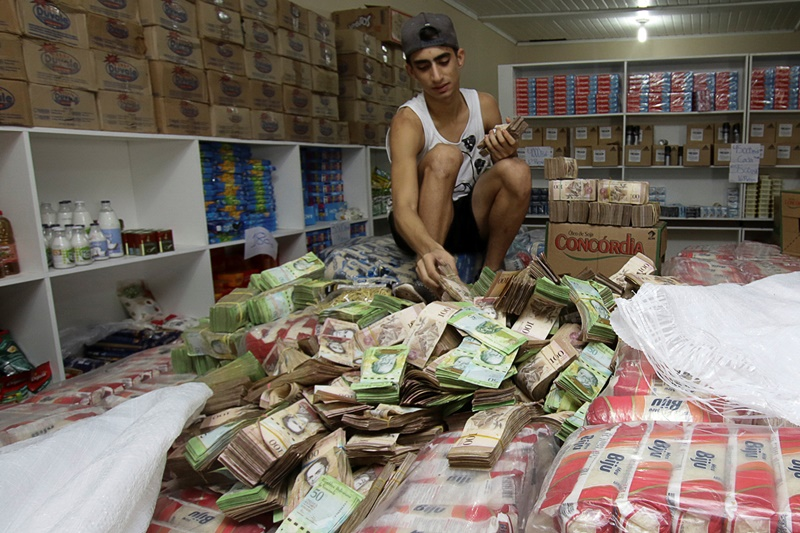 A man counts Venezuelan bolivar notes at a store that sells staple items and food in Pacaraima, Brazil August 3, 2016. Picture taken August 3, 2016. REUTERS/William Urdaneta FOR EDITORIAL USE ONLY. NO RESALES. NO ARCHIVES.