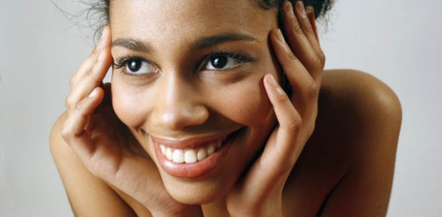 Woman smiling with both hands on face