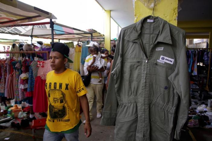 A boy walks past a PDVSA's overall for sale at a market in Maracaibo