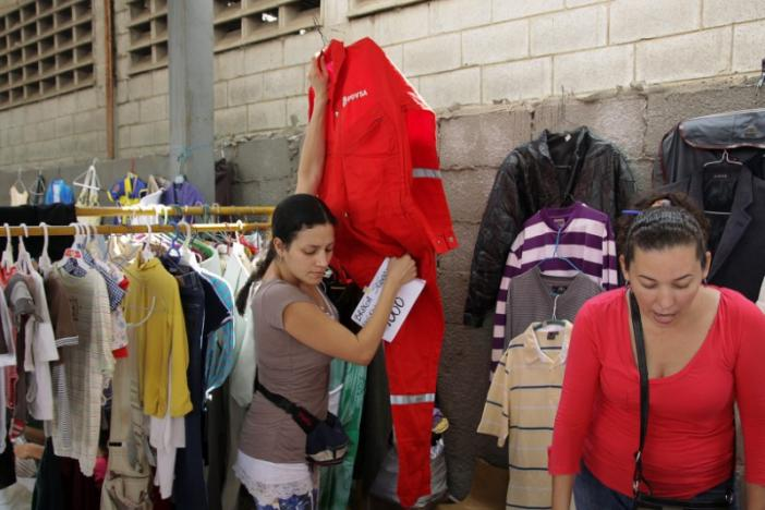 A woman carries a PDVSA's overall for sale at a market in Maracaibo, Venezuela September 11, 2016. REUTERS/Jesus Contreras